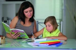 Portrait d'une femme aidant une petite fille à faire ses devoir